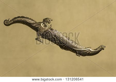 decorative carved dagger with heads of dragons in a sheath on a gray background