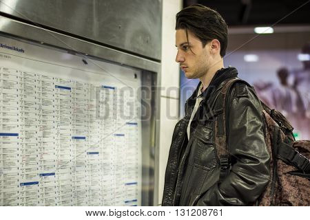 Young man traveling, standing next to train timetable in railway station