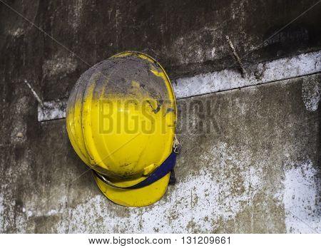 yellow construction helmet hanging on hat rack.