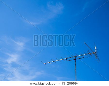 Classic style antenna with clear blue sky.