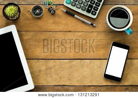 Office workspace with blank screen tablet blank screen smartphonecoffee cup pencil calculator and compass.Top view with copy space