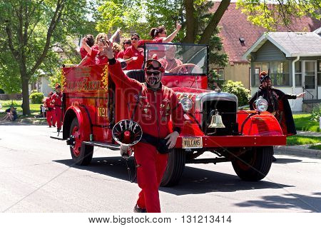 WEST ST. PAUL, MINNESOTA - MAY 21, 2016: Vulcan Krewe of Winter Carnival lore and supporters in red fire truck wave to crowd during annual West St. Paul Days Grande Parade in West St. Paul on May 21, 2016.