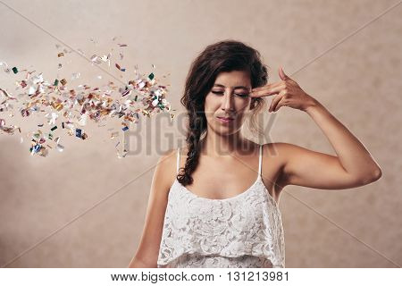 Young woman pretending to shoot herself, sparkles falling out of her head