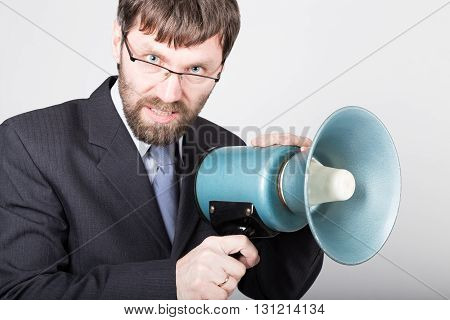 bearded businessman yelling through bullhorn. Public Relations. man expresses various emotions. photos of young businessman wearing a suit and tie.