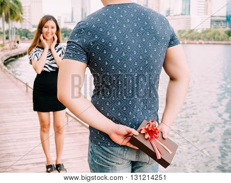 Man Surprises His Girlfriend By Giving Out A Gift - Love And Relationship Concept