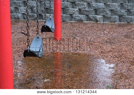 Rainy day at the park playground, red and black swing set