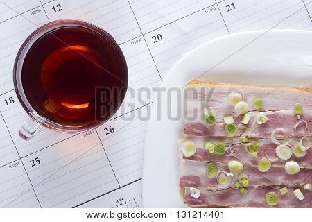 Fresh open sandwich and tea in the background as the calendar