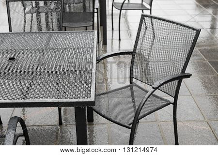Black wrought iron patio set in the rain