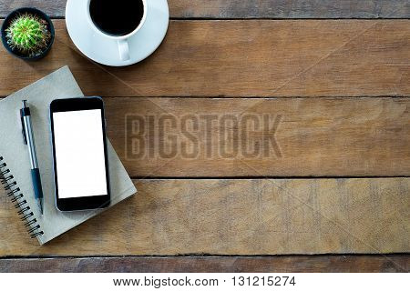 Office desk table with blank screen smartphone notebook pen and coffee cup .Top view with copy space
