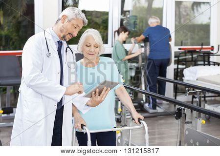 Doctor Showing Reports On Digital Tablet To Woman Using Walker