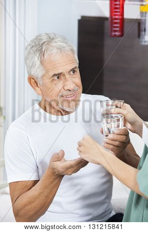 Nurse Giving Medicine And Water Glass To Patient