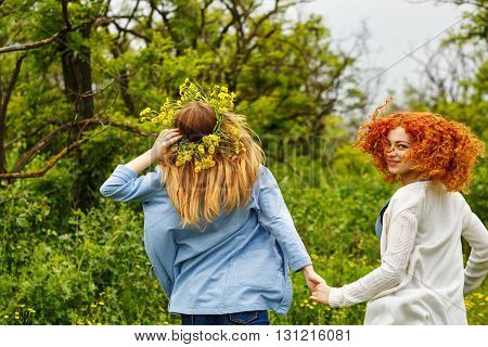 Best friends forever. Girlfriends strolling hand in hand. BFF. Walk. The girl on a head a wreath of wildflowers. Go away.