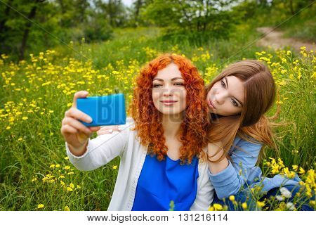 Best friends forever. Girlfriends doing selfie phone in the park. BFF. Close friends. Gentle friendship.