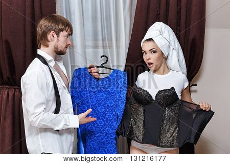 Morning couples. Husband and wife are going to the party. The man holding her dress. Girl holds a corset with a towel on his head. Family time.