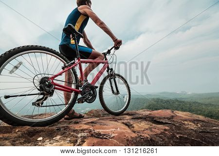 The man with the bike standing on the top of mountain