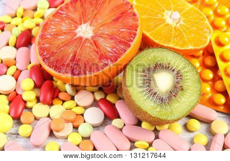 Fresh natural fruits and pills tablets or capsules choice between healthy nutrition and medical supplements