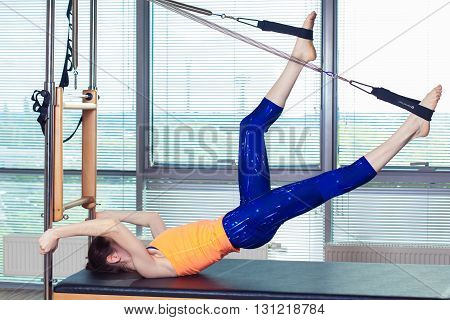 Healthy Smiling Woman Wearing Leotard Practicing Pilates in Bright Exercise Studio.
