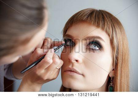 makeup artist glues false eyelashes to young beautiful woman