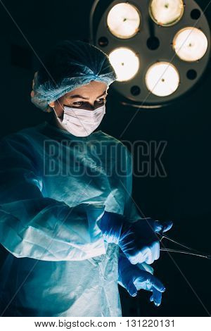Surgeons working with Monitoring of patient in surgical operating room. breast augmentation.