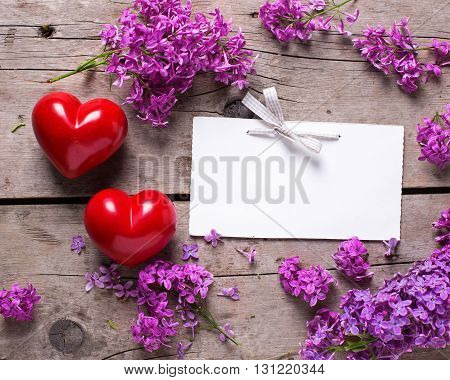 Fresh violet lilac flowers decorative red hearts and empty tag on aged wooden planks. Selective focus. Place for text. image.