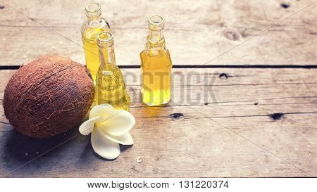Bottles with coconut oil on vintage wooden background. Selective focus. Place for text. Toned image.