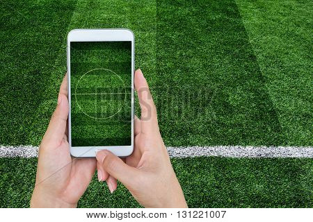 Hand holding mobile smart phone with football stadium image of a football field as background.
