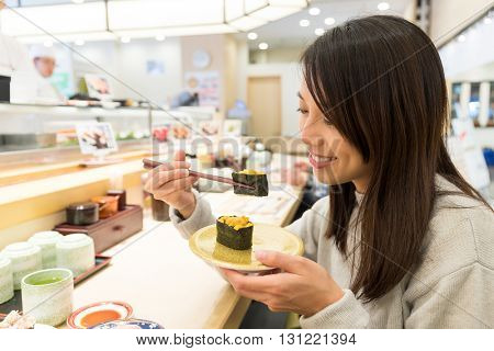 Woman having sushi in restaurant