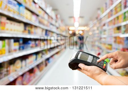Hand hold credit card machine on supermarket store blur background with bokeh