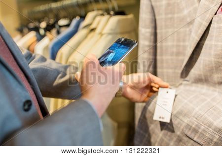 sale, shopping, fashion, technology and people concept - close up of man in suit with smartphone choosing clothes at clothing store