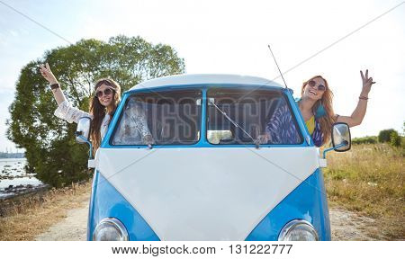 summer holidays, road trip, vacation, travel and people concept - smiling young hippie women driving minivan car and showing peace gesture