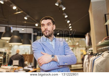 sale, shopping, fashion, style and people concept - happy young man or businessman in jacket and wristwatch at clothing store