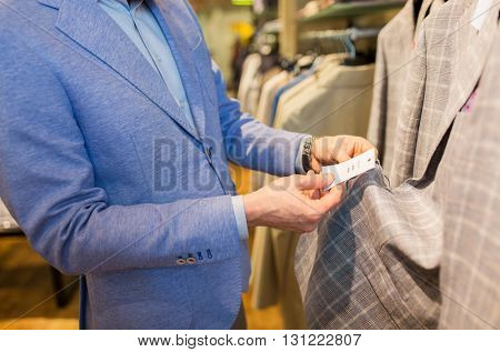 sale, shopping, fashion, style and people concept - close up of elegant young man in jacket choosing clothes and looking at price tag in mall or clothing store
