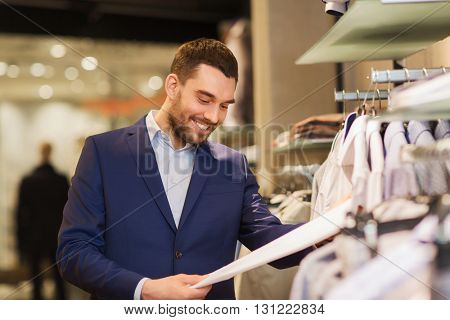 sale, shopping, fashion, style and people concept - happy elegant young man in suit choosing clothes in mall or clothing store