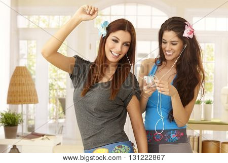 Happy girls listening to music on mp3 player, dancing at home in living room, smiling.