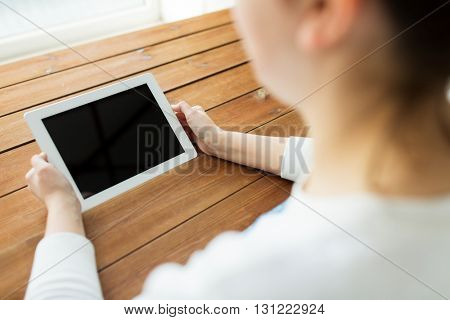 technology, people and advertisement concept - close up of woman with blank tablet pc computer screen on wooden table