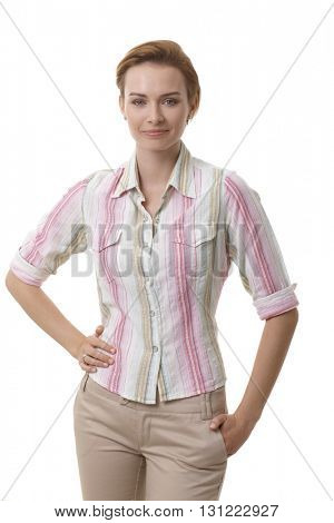 Attractive young woman in casual clothes standing hand on hip, smiling.