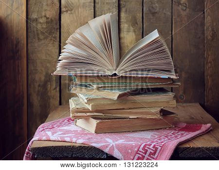 A stack of books on a wooden table. An open book. Still life with books.