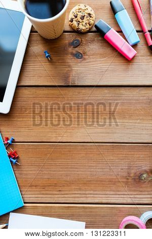 education, school supplies, art, creativity and object concept - close up of stationery and tablet pc computer with coffee cup on wooden table