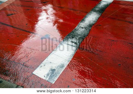 weathered stop line on the red asphalt pavement in TokyoJapan