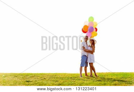 love, wedding, summer, dating and people concept - smiling couple wearing sunglasses with balloons hugging outdoors
