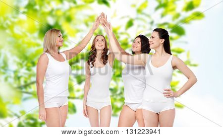gesture, friendship, beauty, body positive and people concept - group of happy different women in white underwear making high five over green natural background
