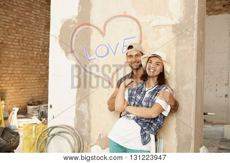 Happy loving couple embracing at home under renovation.