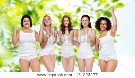 success, friendship, beauty, body positive and people concept - group of happy plus size women in white underwear celebrating victory over green natural background