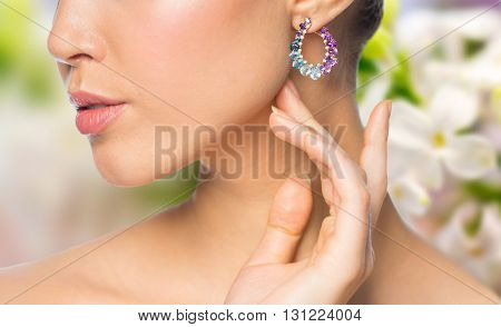 glamour, beauty, jewelry and luxury concept - close up of beautiful woman face with earring over natural spring lilac blossom background