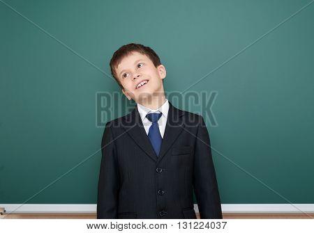school boy in black suit portrait on green chalkboard background, education concept