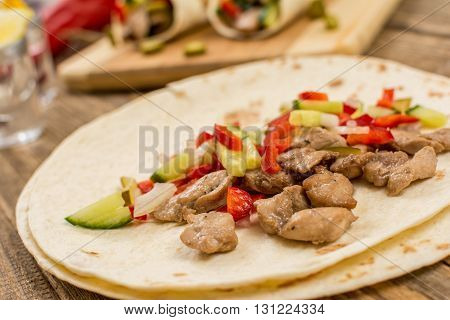 Traditional mexican tortila wrap with meat and vegetables