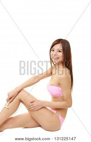 young Japanese woman in a pink bikini shaving legs
