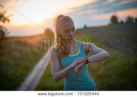 young woman jogger ready to run set and looking at sports smart watch, checking performance or heart rate pulse trace. Sport and fitness outdoors