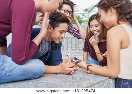 Group of Vietnamese young people gathered at smartphone of friend
