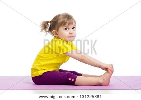 Child girl doing fitness exercises on gymnastic mat